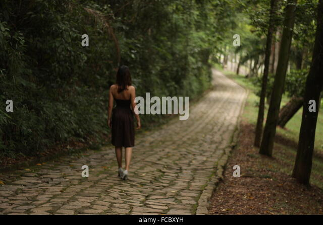 Rear View Of Woman Walking On Pathway Along Trees - Stock Image