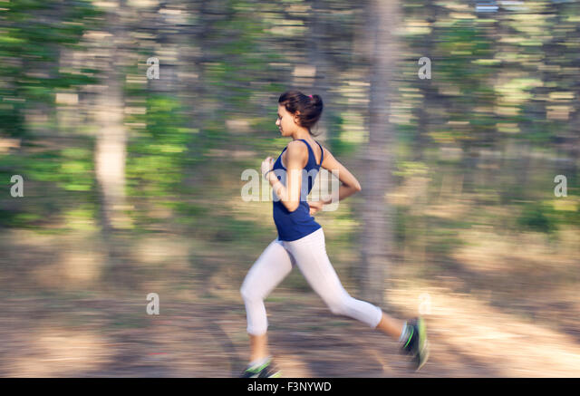Young woman running on a rural road at sunset in autumn forest. Lifestyle sports background - Stock Image