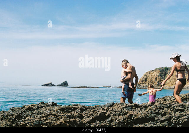 A family on holiday, two adults with their son and daughter walking across rocks by the ocean. - Stock Image