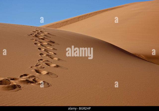 footprints on sand dune with blue sky - Stock Image
