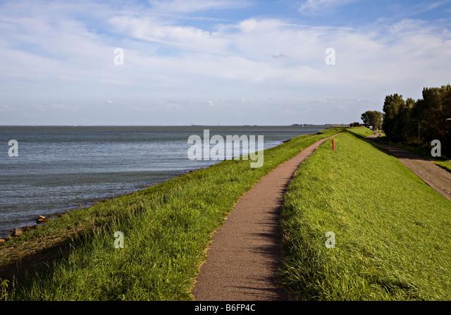 Dyke with footpath alongside Zuiderzee near town of Edam Netherlands - Stock Image