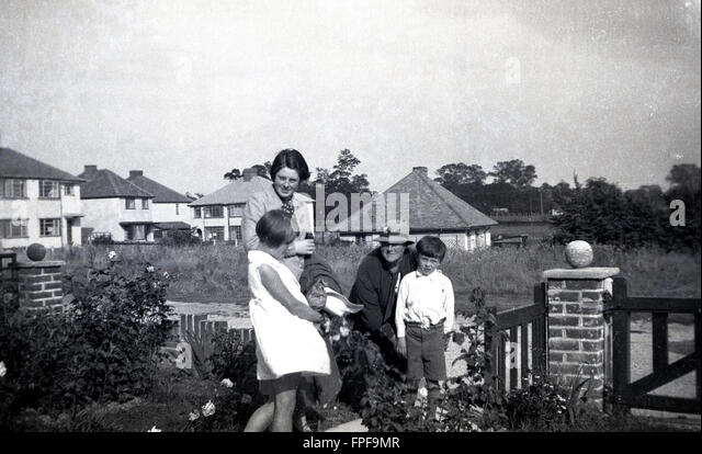 1930s historical, mother, grandmother and children at entrance to house, England. - Stock Image