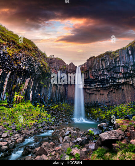 Summer scene of famous Svartifoss (Black Fall) Waterfall. Colorful sunrise in Skaftafell, Vatnajokull National Park, - Stock Image
