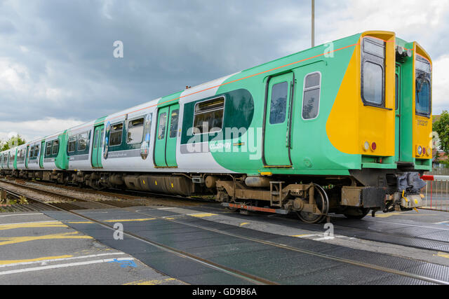 Southern Railway train going through a level crossing in West Sussex, England, UK. Southern Rail. Southern train. - Stock Image