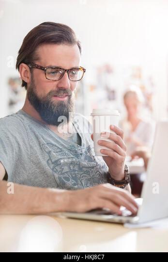 Male design professional drinking coffee working at laptop - Stock-Bilder