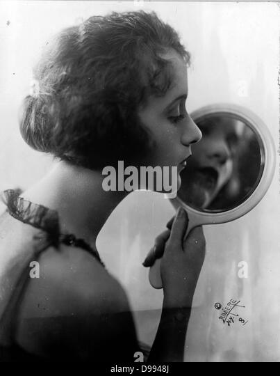 Constance Talmadge, American Silent Movie actress, looking into mirror 1921 - Stock-Bilder