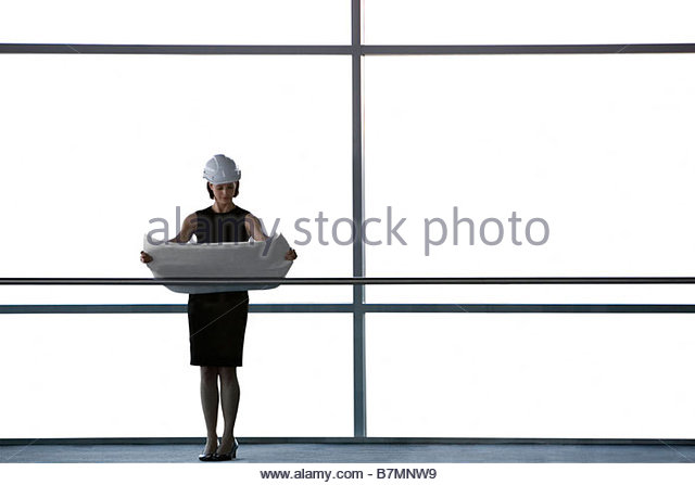 An architect or developer standing on walkway of office building, looking at plans - Stock-Bilder