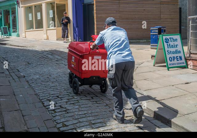 Postman Pushing Heavy Royal Mail Cart Up Hill - Stock Image