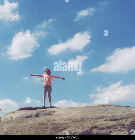 Girl stands on top of rocks in the Peak District; blue sky and fluffy clouds in the background. - Stock Image