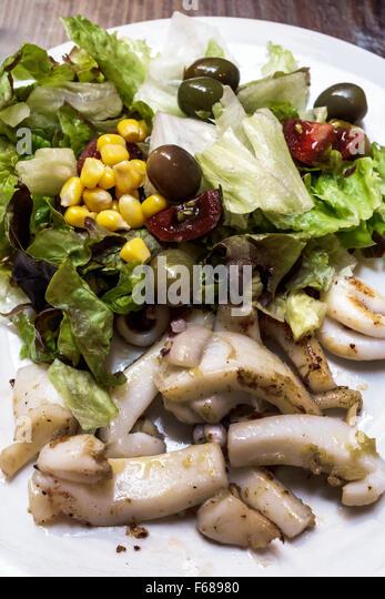 Spain Europe Spanish Hispanic Toledo Cerveceria Gambrinus bar restaurant business squid salad olive plate lunch - Stock Image