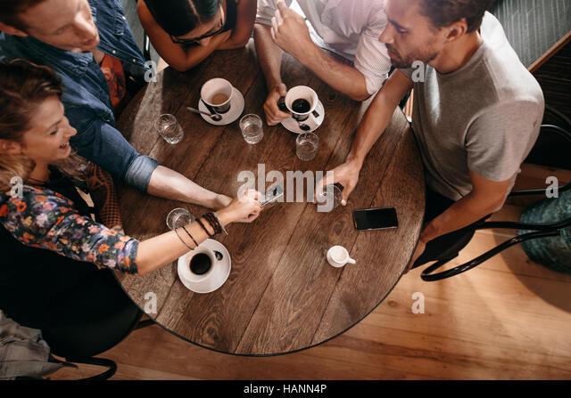 Top view of young people sitting around a cafe table and looking at mobile phone. Young men and women looking at - Stock Image