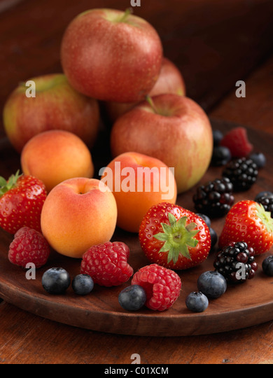 A pile of fresh ripe fruit apples strawberries blueberries blackberries raspberries and apricots - Stock Image