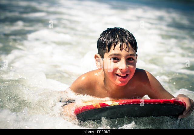 Boy (10-11) surfing in sea - Stock Image