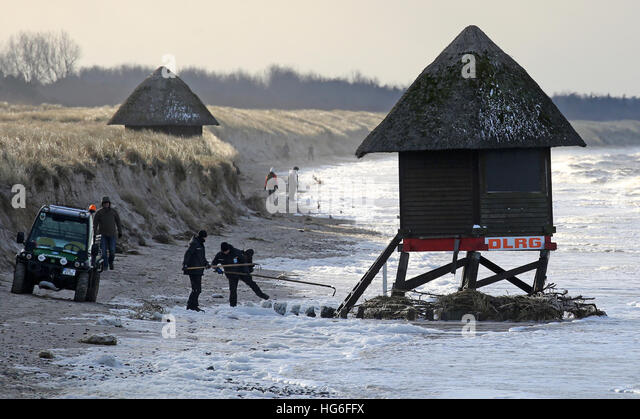 Graal-Mueritz, Germany. 05th Jan, 2017. Workers look at a severely damaged lifeguard's tower on the Baltic coast - Stock-Bilder