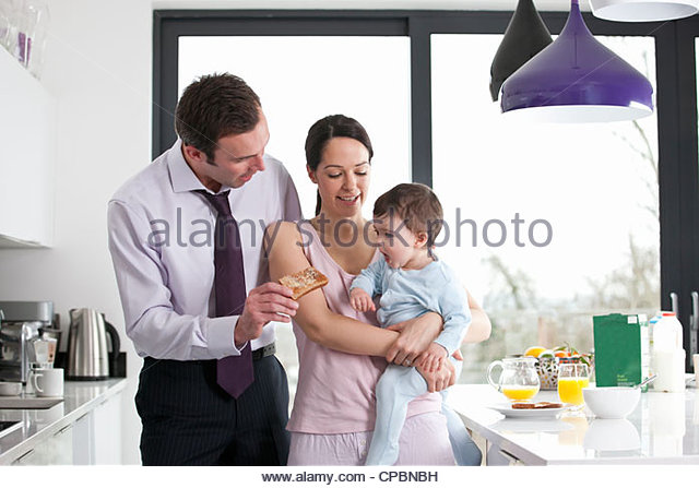 A couple and their baby son in the kitchen at breakfast time - Stock-Bilder