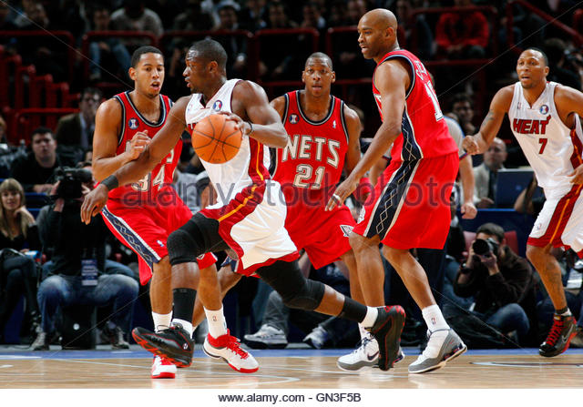 Miami Heat guard Dwyane Wade (2nd L) drives the ball against against New Jersey Nets Devin Harris (L), Bobby Simmons - Stock Image