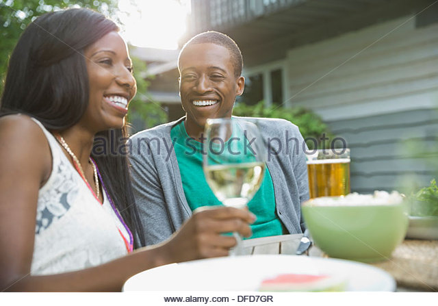 Cheerful couple enjoying a drink outdoors - Stock Image