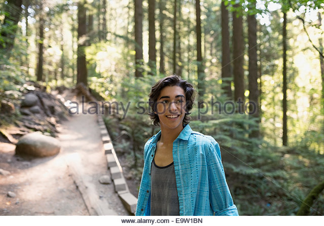 Teenage boy on path in woods - Stock Image