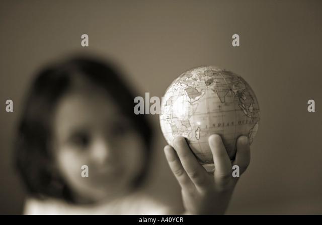 Little girl holds world in hand - Stock Image