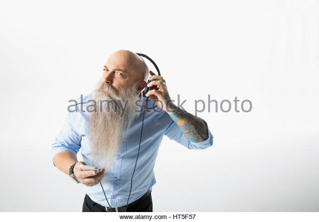 Portrait hipster businessman with beard listening to music with headphones against white background - Stock-Bilder