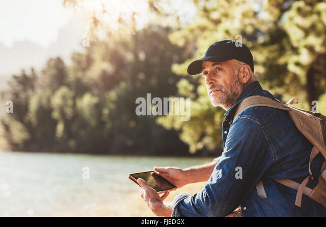 Portrait of senior man sitting near a lake with backpack and digital tablet. Mature male hiker sitting at a lake - Stock Image