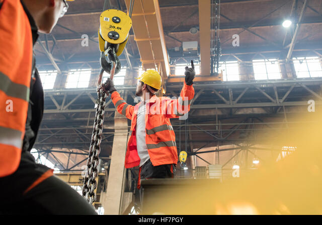 Steel workers fastening chain to crane in factory - Stock Image