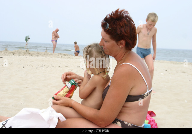 Adult woman overweight in bikini at beach feeding her daughter junk food potato crisps at the beach. - Stock-Bilder