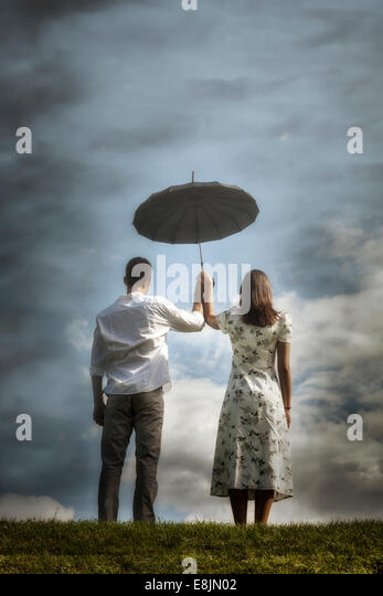 a couple on a meadow with an umbrella - Stock Image