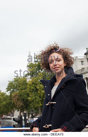 Woman in wool coat walking in city - Stock Image