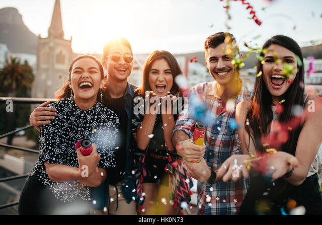 Group of friends enjoying party and throwing confetti. Friends having fun at rooftop party. - Stock Image