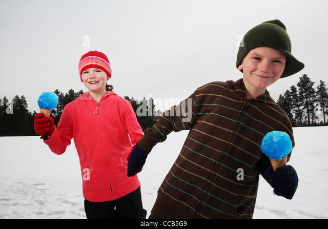 Two children eating snow cones on a winter day - Stock Image