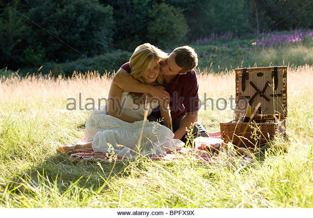 A young couple having a picnic, embracing - Stock Image