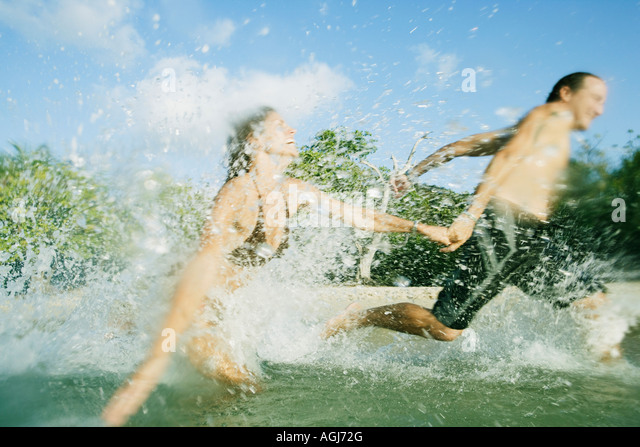 Mid adult couple running in water on the beach - Stock Image