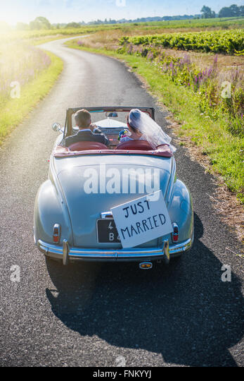 A newlywed couple is driving a retro car on a country road for their honeymoon - Stock Image