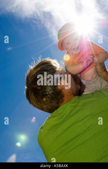 Father lifting baby daughter up towards the sun. - Stock Image