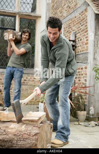 Man chopping wood with axe - Stock Image