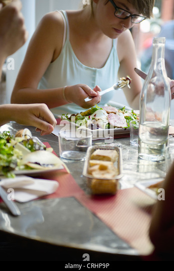 Young woman eating meal in cafe - Stock-Bilder