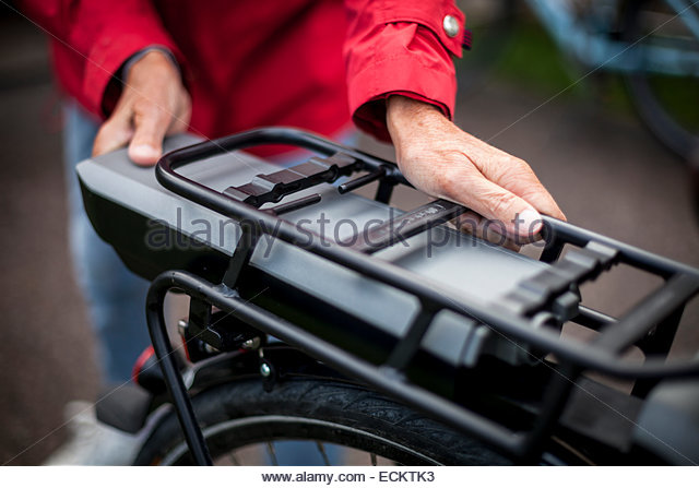 Midsection of senior woman inserting battery in backseat of electric bicycle - Stock Image