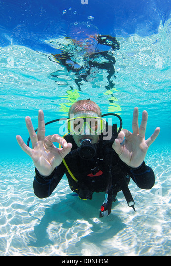 A scuba diver signals 'OK' in clear waters of the shallows, North Huvadhu Atoll, the Maldives. - Stock Image