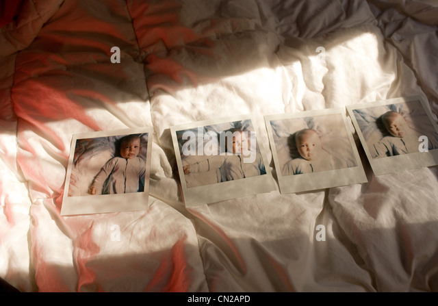 Instant film photograph of baby boy on bed - Stock Image