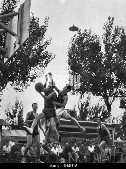 Workers playing and watching a game of basketball after work during the Cultural Revolution era in Communist China. - Stock Image