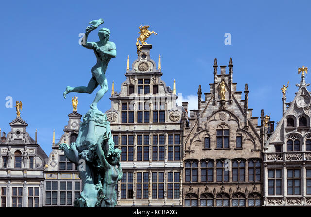 Antwerp - Belgium. Statue of Silvius Brabo throwing the giants hand towards the 16th century Guildhouses of the - Stock Image