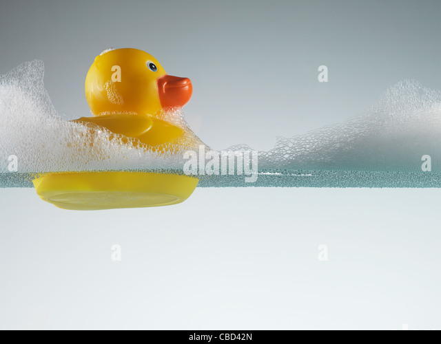 Rubber duck floating in soapy water - Stock Image