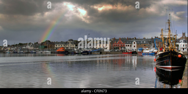 Stornoway Harbour with a Rainbow over the town of Stornoway in the western Isles of Scotland, United Kingdom - Stock Image
