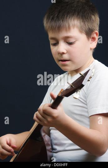 Boy in white playing balalaika - Stock Image