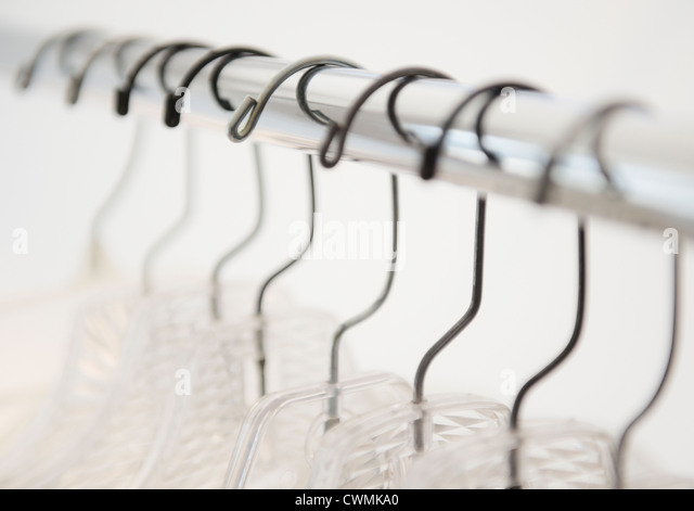 Coat hangers on clothes rack - Stock Image