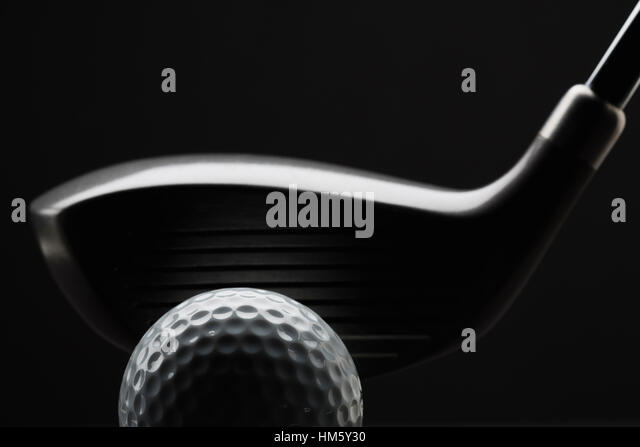Close-up view of golf ball and club on black background - Stock Image