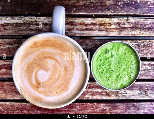 Cup of cappuccino and glass of green juice on rustic wooden table - Stock Image