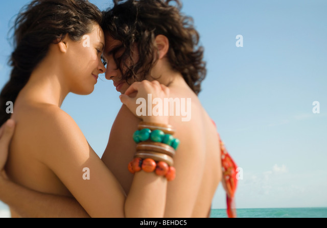 Side profile of a young couple romancing on the beach - Stock-Bilder
