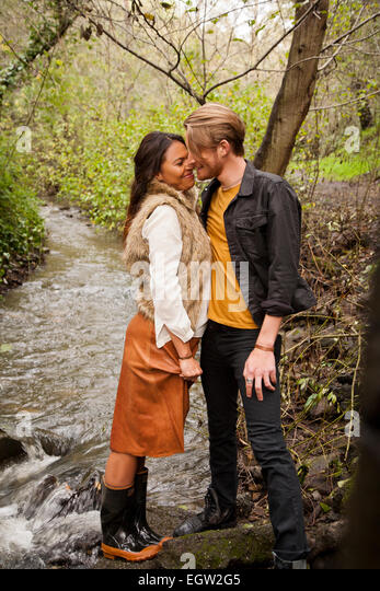 Woman and man about to kiss near creek. - Stock Image